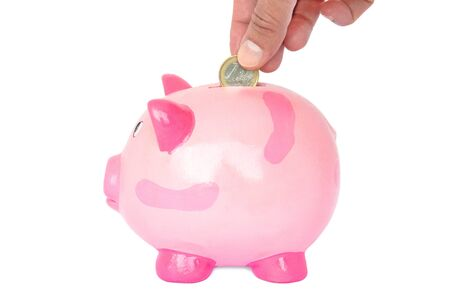 financials: Female hand dropping one euro coin into a pink piggy bank