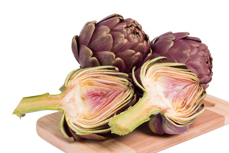 green and purple vegetables: Fresh sliced artichokes on a wooden cutting board Stock Photo