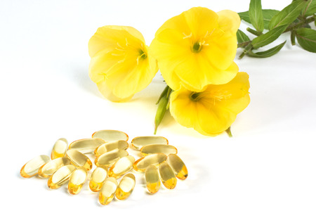 primrose oil: Evening primroses near yellow gelatin capsules on white background