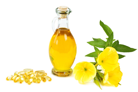 evening primrose oil: Evening primroses with gelatine capsules and oil bottle on white background