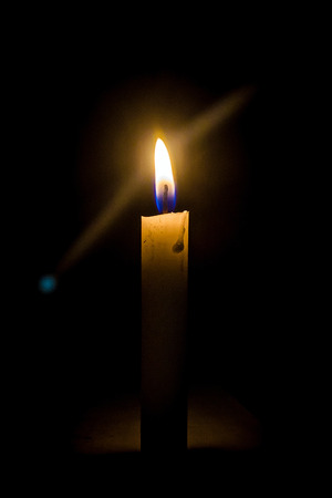 a candle in the night in the photo on the wall with light dimly lit Stock Photo