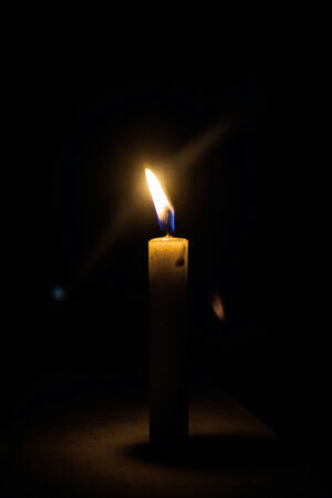 dimly: a candle in the night in the photo on the wall with light dimly lit Stock Photo