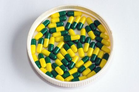 green yellow capsule drug isolated white background