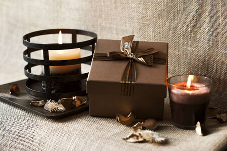 Golden-brown gift box with candles on wooden plate  Burlap sack backround Archivio Fotografico