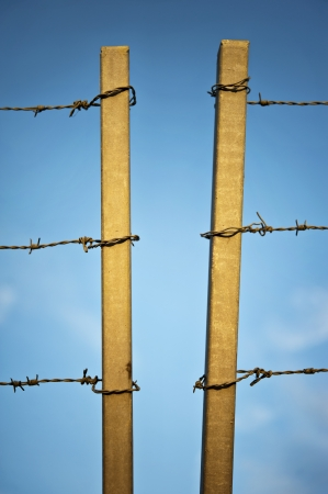 Barbed wire with two concrete columns on blue sky background Stock Photo
