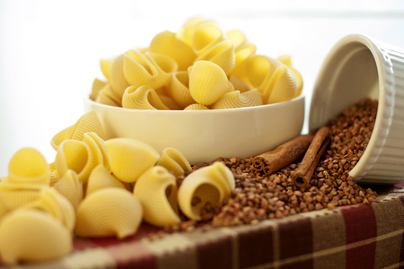 scatter: White porcelain plates with dry Snailshell-shaped pasta and scattered buckwheat, close-up