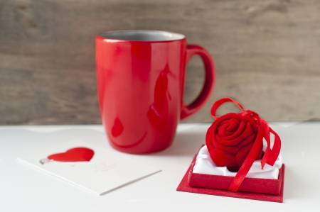 Valentine gift box with greeting card and red cup on wooden background  Close-up photo