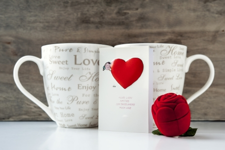 Valentine gift box with greeting card and two cups on wooden background  Close-up photo