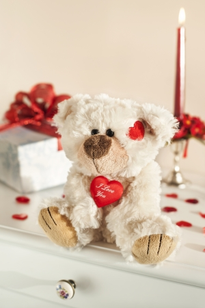 Teddy bear, gift box and red candle on background.  photo