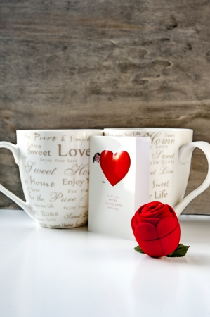 Valentines day gift box with greeting card and two cups on wooden background. Close-up photo