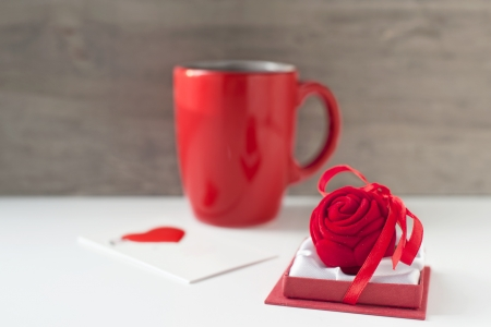 Valentine gift box with greeting card and red cup on wooden background. Close-up photo