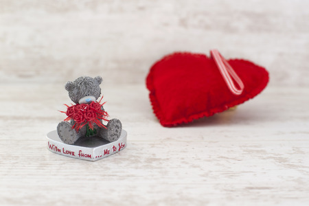 valentine s day teddy bear: Miniature valentine s day teddy bear and red heart on gray wooden