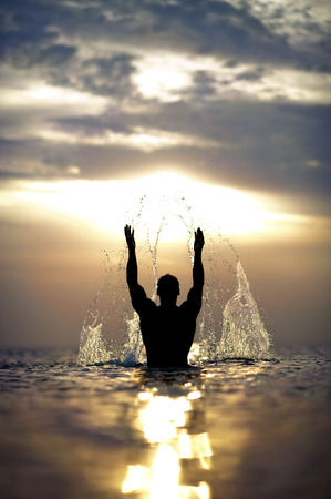 Athletic Man s silhouette with raised hands out of the sea with splash  Stock Photo