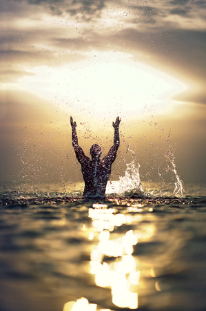 Athletic Man s silhouette with raised hands out of the sea with splash  photo