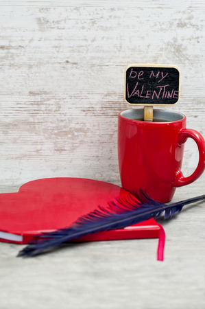 Red cup, heart shaped notepad and quill  Valentine photo