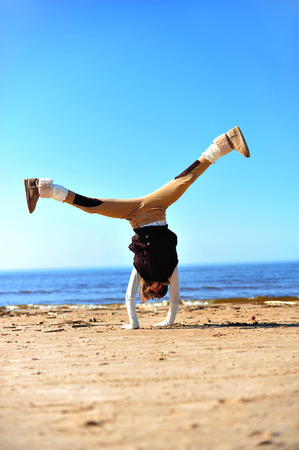 happines: Girl doing handstand on the sunny beach