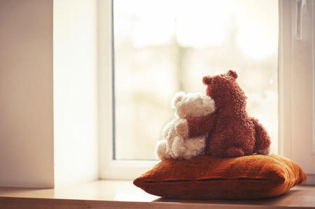 Two embracing teddy bears looking through the window sitting on window-sill  Stock Photo