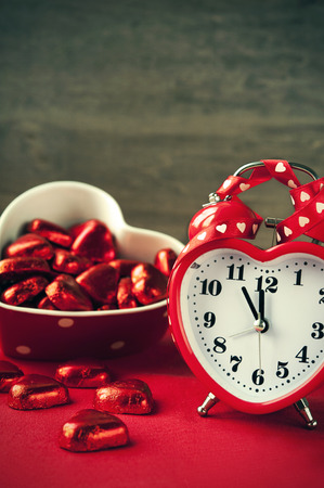 Valentine heart shaped red love clock with chocolates  Time for sweet love  photo