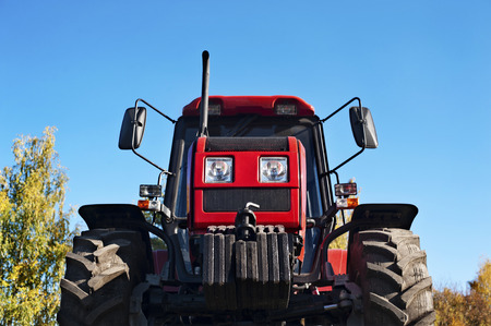 Modern red tractor on a blue sky background photo