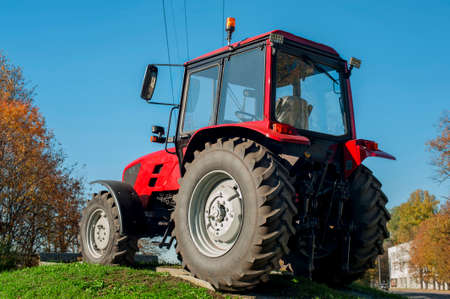 Modern red tractor on a blue sky background  Outdoors photo