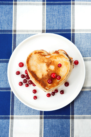 Love heart pancakes with cranberries on white  porcelain plate. Morning celebration breakfast. Closeup.
