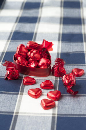Heart shaped red metal box full with many sweet chocolates.  photo