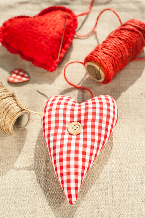 Homemade sewed couple red cotton love heart. Indoor closeup. photo