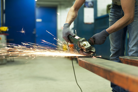 Industry-man hands sawing metal with sparks in workshop. Metalworking. photo