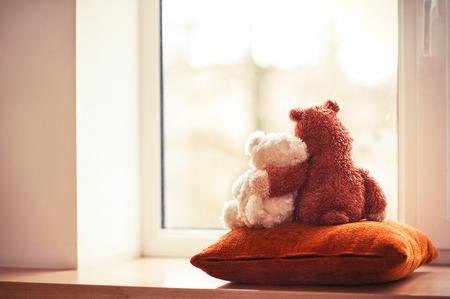 Two embracing loving teddy bear toys sitting on window-sill