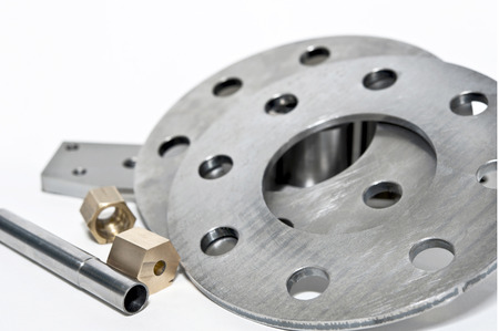 Closeup metal flanges and brass nuts  CNC milling and lathe industry