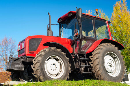 Modern red tractor outdoors photo