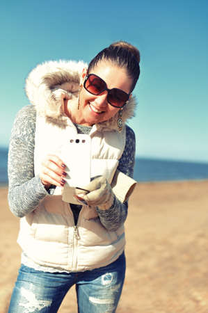 Smiling young woman with mobile phone on the beach photo