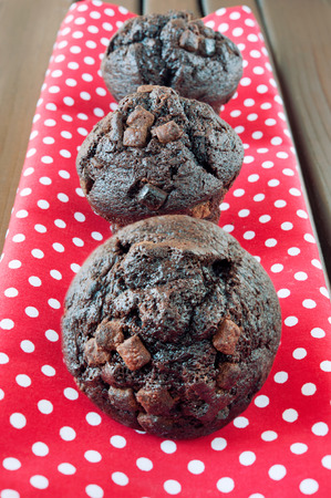 stil: Homemade chocolate muffins on red spotted napkin  Wooden