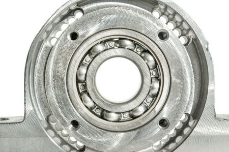 mounting holes: Metal mounted roller bearing unit CNC technology. Milling lathe and drilling industry. Metalworking. Mechanical engineering. Indoors closeup.