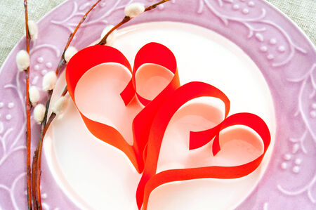 Two paper red hearts with willow twig on porcelain plate. Indoors closeup. photo