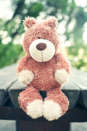 sorrowfully: Lonely sad forgotten teddy bear toy on wooden table in the park. Awaiting for owner. Vintage filter. Outdoors. Stock Photo