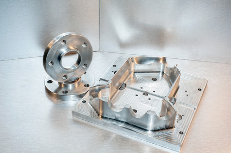 mounting holes: Metal mold blank and steel flanges  Milling industry  CNC technology  Stock Photo