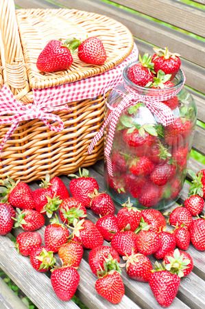 bounty: Muchos de fresa fresca madura en la cesta y el vaso de vidrio sobre fondo de madera. Cosecha de verano Bounty en el jard�n. Aire libre. Foto de archivo