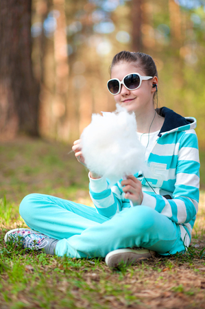 Smiling happy girl in sportswear in spring park eating cotton candy  Treat and happiness  photo