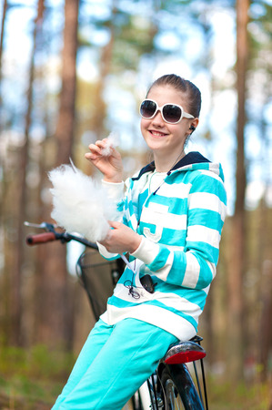 Smiling happy girl in sportswear in spring park eating cotton candy  Outdoors  photo