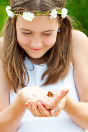 be careful: Love the nature be careful  Small butterfly in girl hands  Outdoors  Stock Photo