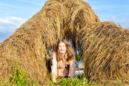 hayrick: Happy playing smiling girl crawling out from hayrick in summer field. Carefree childhood. Sunshine outdoors. Stock Photo