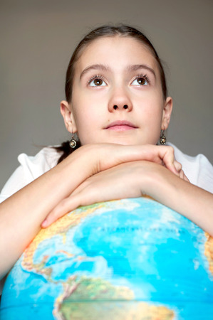 gladden: Back to school. Smiling thoughtful schoolgirl with blue round globe dreaming about the future. Childhood and education. Stock Photo