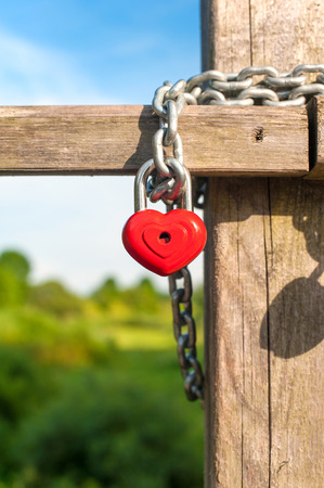Love heart shape lock with metal chain on wooden bridge. Outdoors closeup on blue sky background. Stock Photo