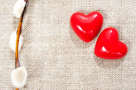 Couple red plastic shiny love hearts with spring willow twig on burlap background. Indoor closeup.