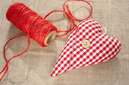 Homemade sewed red cotton love heart. Indoor closeup. photo