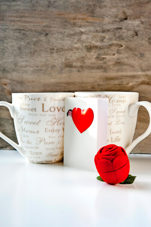 Valentine gift box with love greeting card and two coffee cups on wooden background. Indoors close-up photo