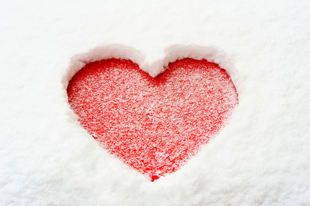 valentine's day: Valentine love red heart shape in snow on red car hood. Outdoors. Closeup. Stock Photo