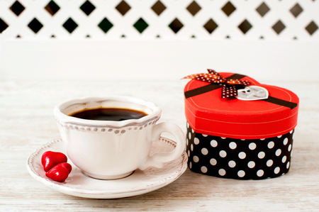 valentine day cup of coffee: Valentine s day celebration porcelain cup of coffee with red heart shaped gift box. Indoors still-life.