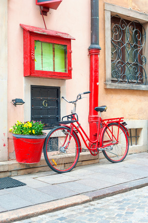 original bike: Red rustic retro bicycle close to stone wall.  Outdoors.